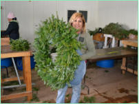"One of our wreath workers holding a 36"" Fraser Fir Wreath"